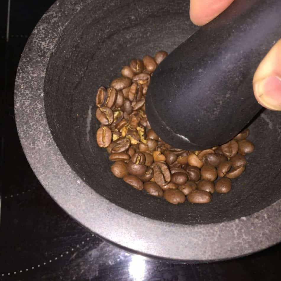Grinding coffee with a mortar and pestle