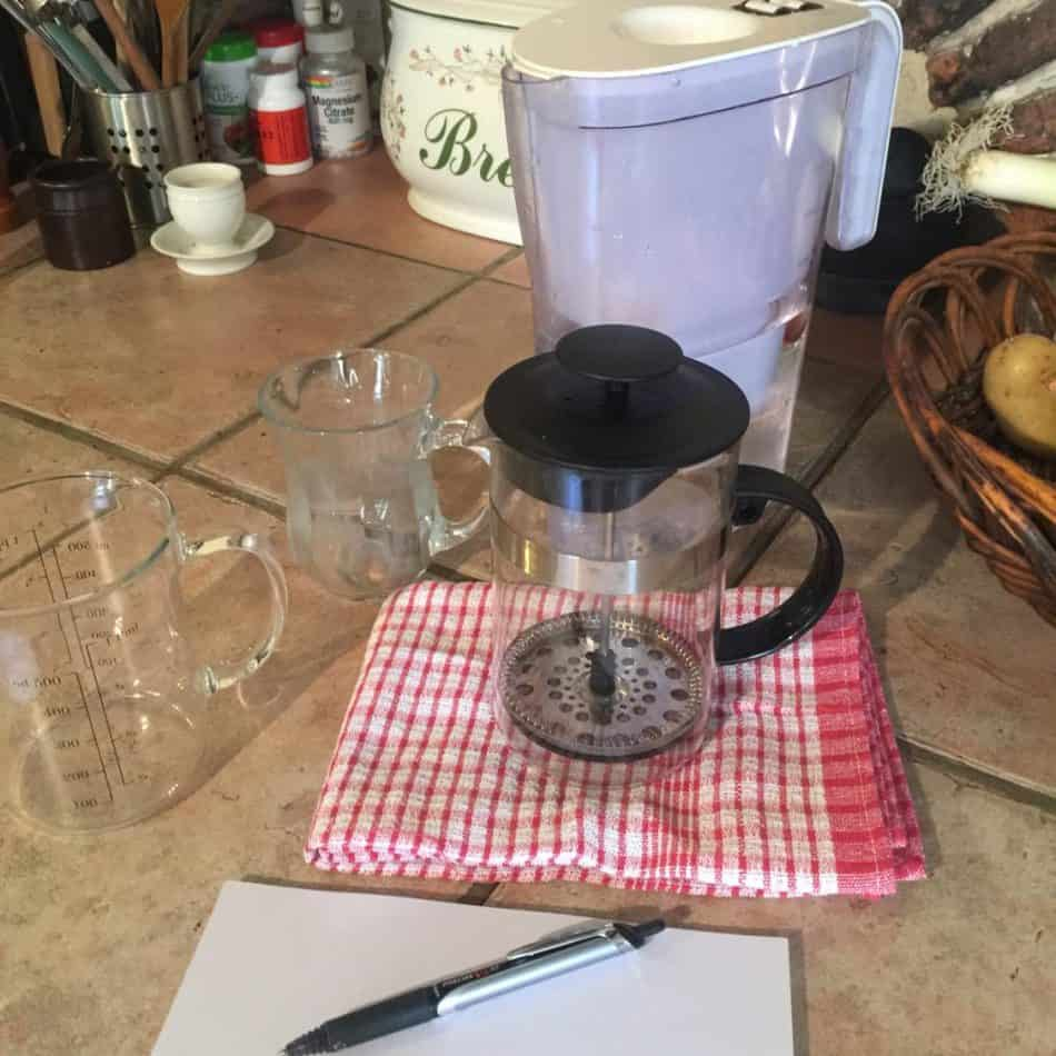 French press, measuring cup, cup, and writing utensils.